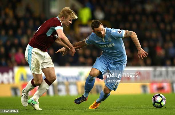 Ben Mee of Burnley and Marko Arnautovic of Stoke City battle for possession during the Premier League match between Burnley and Stoke City at Turf...