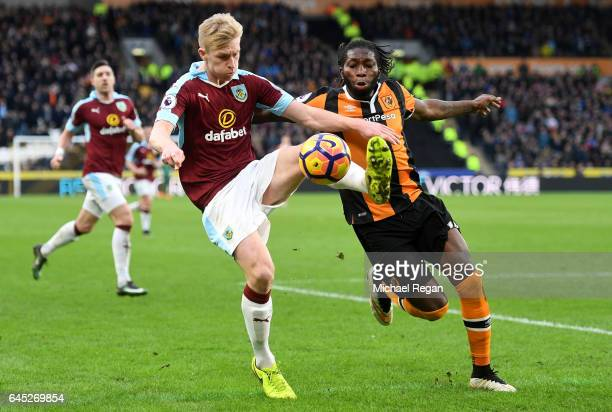 Ben Mee of Burnley clears the ball while under pressure from Dieumerci Mbokani of Hull City during the Premier League match between Hull City and...