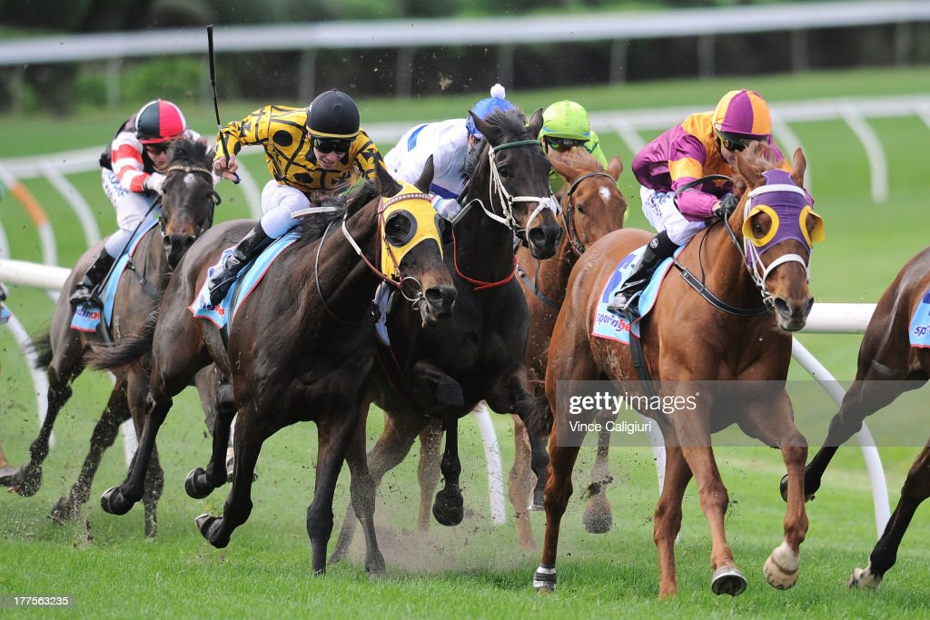 Ben Melham riding Gotta Take Care (L) turns into the home straight to win the ADAPT Australia BM96 Handicap during Melbourne Racing at Moonee Valley Racecourse on August 24, 2013 in Melbourne, Australia.