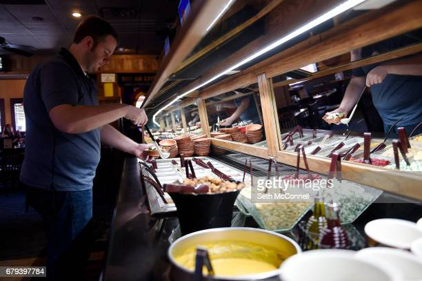 Ben Miller loads up a plate at the salad bar at Woody's WoodFired Pizza on May 4 in Golden Colorado Woody's WoodFired Pizza offers more than just...