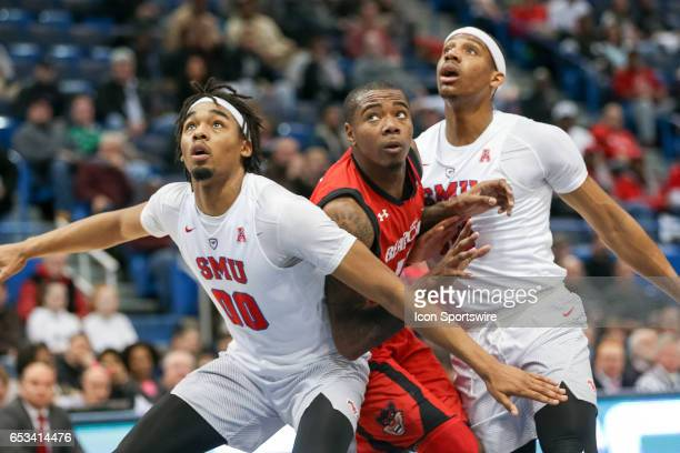 Ben Moore and Jarry Foster of SMU look to block Troy Caupain of Cincinnati off the free throw rebound during the AAC Men's Basketball Championship...