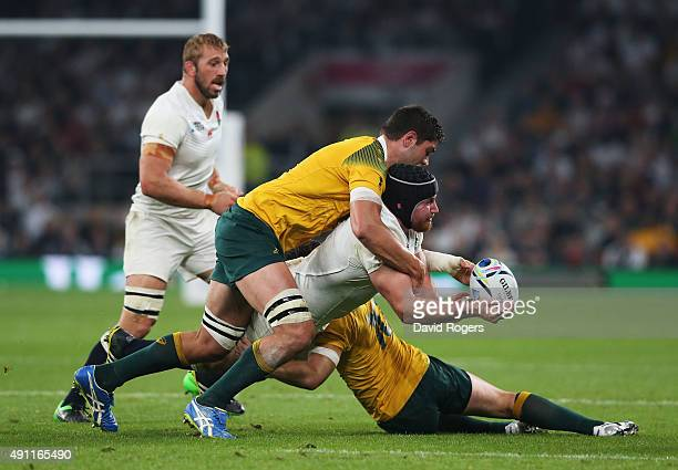 Ben Morgan of England is tackled by Rob Simmons of Australia and Michael Hooper of Australia during the 2015 Rugby World Cup Pool A match between...