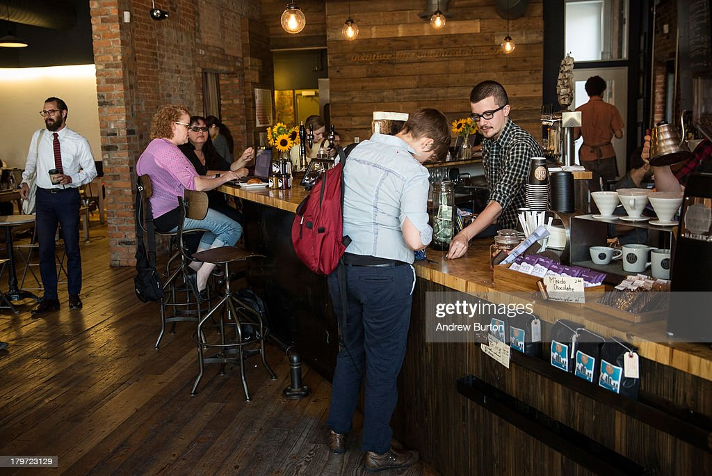 Ben Parenteau (R), a barista at Great Lakes Coffee Roasting Company, helps a customer on September 6, 2013 in Detroit, Michigan. Great Lakes Coffee Roasting opened 14 months ago, and has since become a popular spot for a growing community of creative-types to meet, work on laptops and sip on a coffee or beer. Despite over 78,000 abandoned homes across 140 square miles, 16% unemployment and the city declaring bankrupty in July, Detroit has attracted a booming creative class in the past five years.