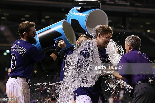 Ben Paulsen of the Colorado Rockies is doused by his teammates Charlie Blackmon and Brandon Barnes as they celebrate his game winning walk off two...