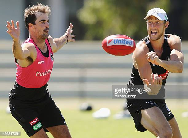 Ben Reid handballs past Steele Sidebottom during a Collingwood Magpies AFL preseason training session at Gosch's Paddock on December 1 2015 in...