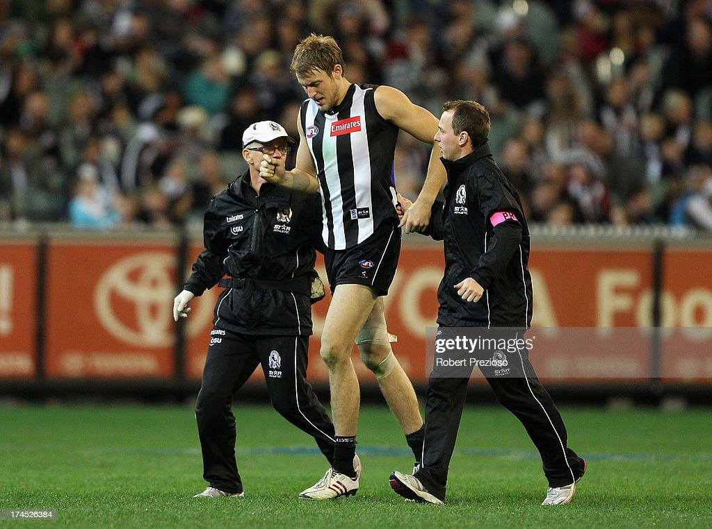 Ben Reid of the Magpies is helped off the ground during the round 18 AFL match between the Collingwood Magpies and the Greater Western Sydney Giants at Melbourne Cricket Ground on July 27, 2013 in Melbourne, Australia.