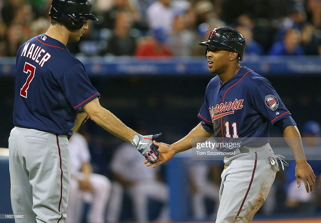 <a gi-track='captionPersonalityLinkClicked' href=/galleries/search?phrase=Ben+Revere&family=editorial&specificpeople=6826641 ng-click='$event.stopPropagation()'>Ben Revere</a> #11 of the Minnesota Twins is congratulated by <a gi-track='captionPersonalityLinkClicked' href=/galleries/search?phrase=Joe+Mauer&family=editorial&specificpeople=214614 ng-click='$event.stopPropagation()'>Joe Mauer</a> #7 after sccoring a run in the seventh inning during MLB game action against the Toronto Blue Jays on October 1, 2012 at Rogers Centre in Toronto, Ontario, Canada.