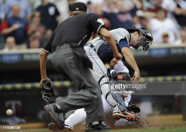 Ben Revere of the Minnesota Twins slides safely into home plate as Alex Avila of the Detroit Tigers defends during in the eighth inning of their game...