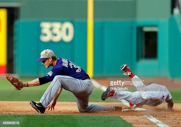 Ben Revere of the Philadelphia Phillies dives into first base before first baseman Justin Morneau of the Colorado Rockies can make the catch for a...