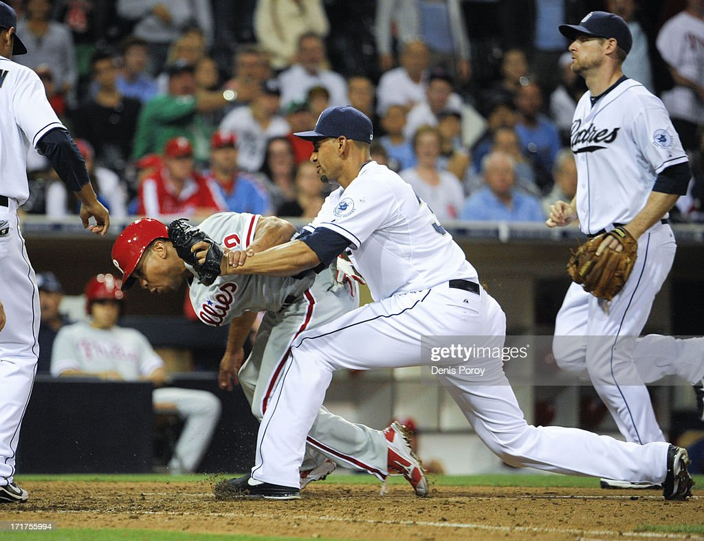 Ben Revere #2 of the Philadelphia Phillies is tagged out by Tyson Ross #38 of the San Diego Padres hits during the 13th inning of a baseball game at Petco Park on June 26, 2013 in San Diego, California. Two runs scored on the play due to an error by Logan Forsythe #11 of the San Diego Padres.