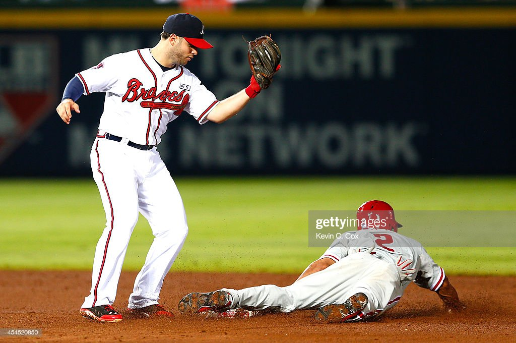 Ben Revere #2 of the Philadelphia Phillies steals second base under Tommy La Stella #7 of the Atlanta Braves in the sixth inning at Turner Field on September 2, 2014 in Atlanta, Georgia.