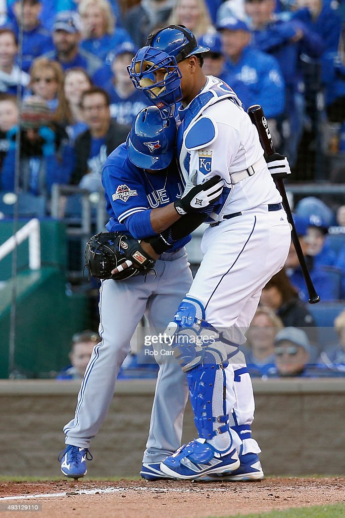 Ben Revere #7 of the Toronto Blue Jays and Salvador Perez #13 of the Kansas City Royals react at home plate after the ball bounces off of Revere's helmet in the seventh inning in game two of the American League Championship Series between the Kansas City Royals and the Toronto Blue Jays at Kauffman Stadium on October 17, 2015 in Kansas City, Missouri.