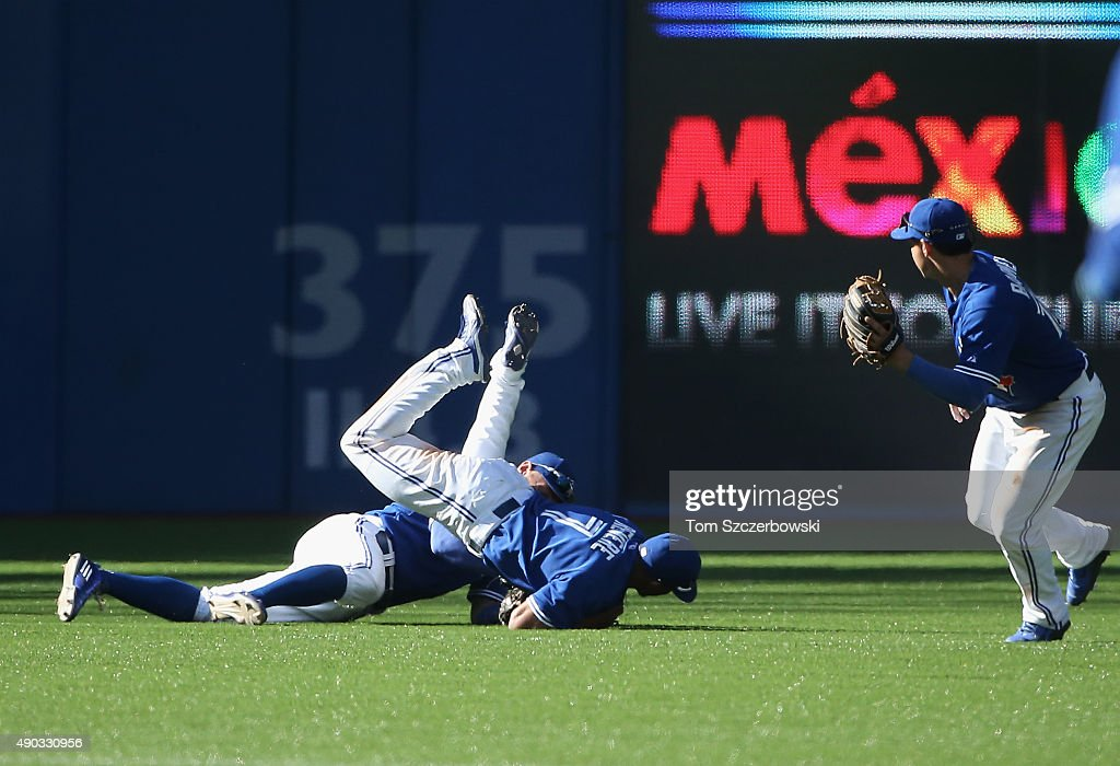 Ben Revere #7 of the Toronto Blue Jays catches a fly ball while colliding with Kevin Pillar #11 in the ninth inning during MLB game action against the Tampa Bay Rays on September 27, 2015 at Rogers Centre in Toronto, Ontario, Canada.