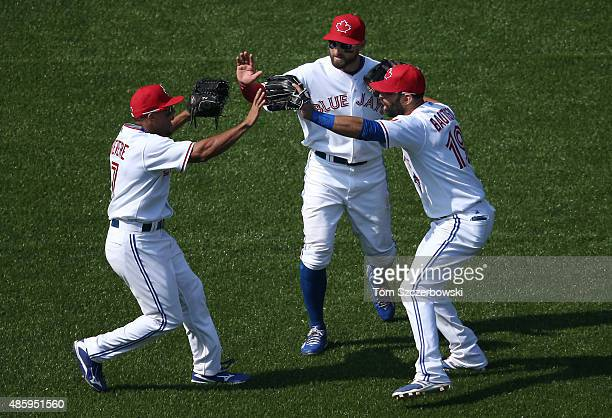 Ben Revere of the Toronto Blue Jays celebrates their victory with Kevin Pillar and Jose Bautista during MLB game action against the Detroit Tigers on...