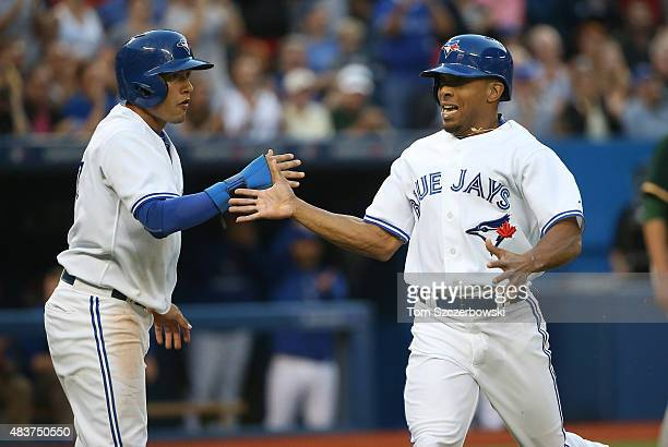 Ben Revere of the Toronto Blue Jays celebrates with Ryan Goins after both runners scored on a tworun single by Josh Donaldson in the second inning...