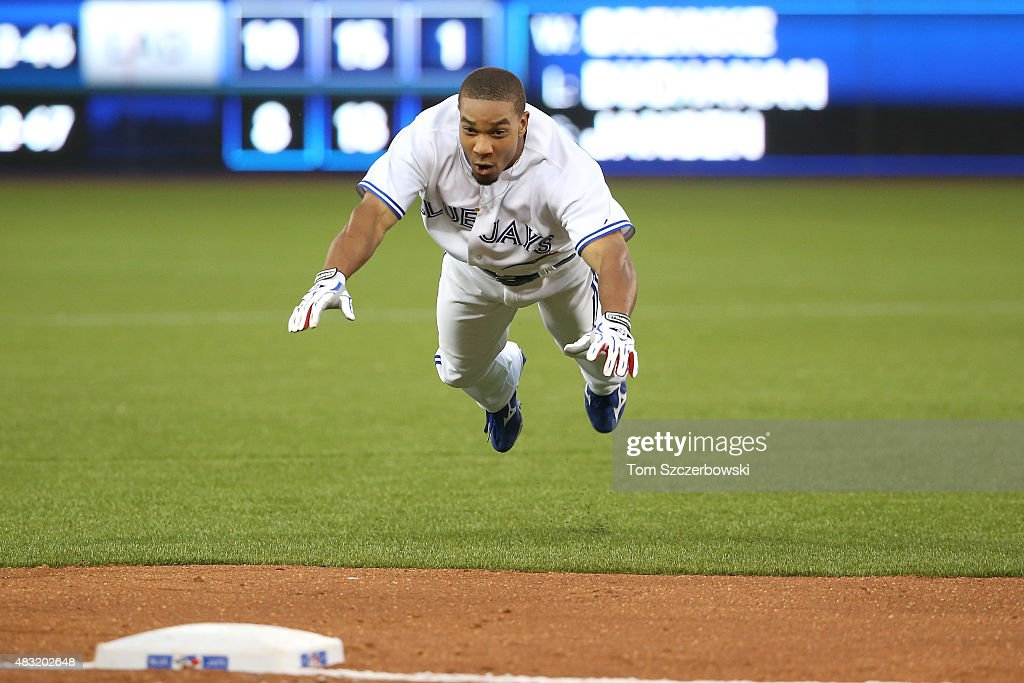 Ben Revere of the Toronto Blue Jays slides safely into third base as he advances on a throwing error following his single in the fifth inning during...