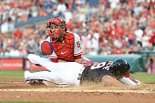Ben Revere of the Washington Nationals beats the tag by Carlos Ruiz of the Philadelphia Phillies on a Jayson Werth triple in the third inning during...