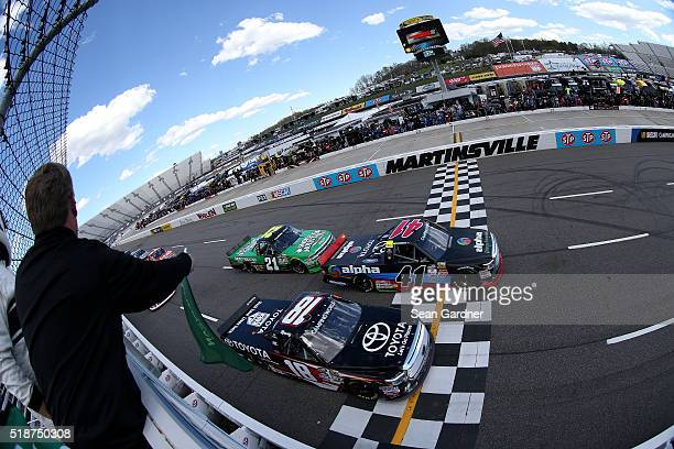 Ben Rhodes driver of the Alpha Energy Solutions Toyota and Kyle Busch driver of the Toyota Toyota lead the field at the start of the NASCAR Camping...
