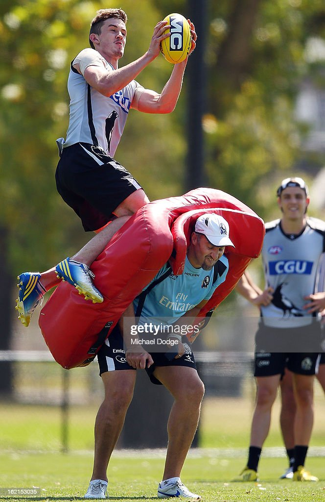 Ben Richond takes a mark over assistant coach Anthony Rocca during a Collingwood Magpies AFL training session at Gosch's Paddock on February 20, 2013 in Melbourne, Australia.