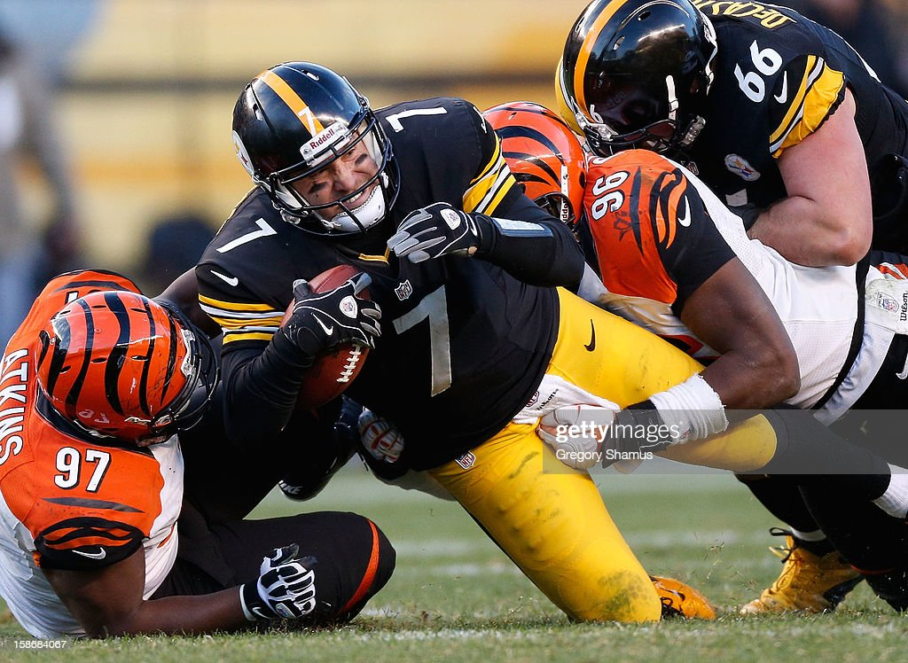 Ben Roethlisberger #7 of the Pittsburgh Steelers is tackled during the fourth quarter by Geno Atkins #97 and Carlos Dunlap #96 of the Cincinnati Bengals at Heinz Field on December 23, 2012 in Pittsburgh, Pennsylvania. Cincinnati won the game 13-10.