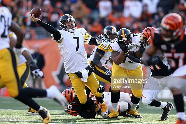 Ben Roethlisberger of the Pittsburgh Steelers throws the ball while getting hit by Carlos Dunlap of the Cincinnati Bengals during the second quarter...