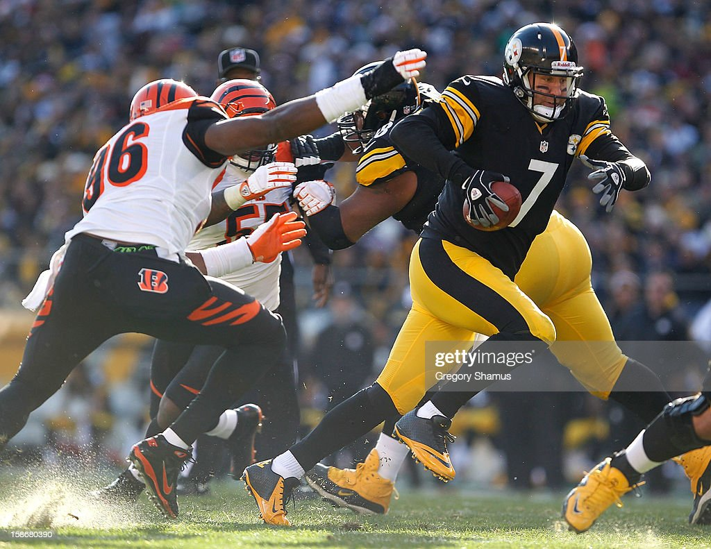 Ben Roethlisberger #7 of the Pittsburgh Steelers tries to outrun the tackle of Carlos Dunlap #96 of the Cincinnati Bengals during the second quarter at Heinz Field on December 23, 2012 in Pittsburgh, Pennsylvania.