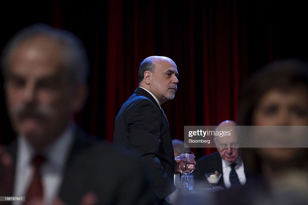 Ben S. Bernanke, chairman of the U.S. Federal Reserve, holds a glass of water after speaking to the Economic Club of New York in New York, U.S., on Tuesday, Nov. 20, 2012. Bernanke said that an agreement on ways to reduce long-term federal budget deficits could remove an impediment to growth, while failure to avoid the so-called fiscal cliff would pose a 'substantial threat' to the recovery. Photographer: Scott Eells/Bloomberg via Getty Images