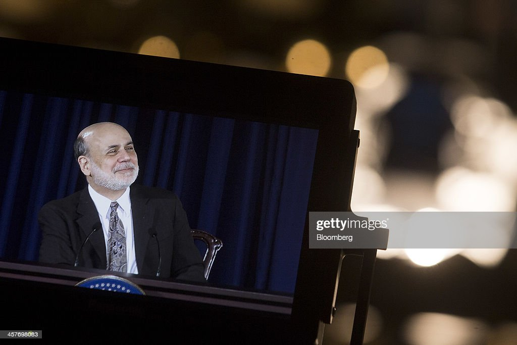 Ben S. Bernanke, chairman of the U.S. Federal Reserve, is seen smiling on a television monitor during a news conference following a Federal Open Market Committee (FOMC) meeting in Washington, D.C., U.S., on Wednesday, Dec. 18, 2013. The Federal Reserve is cutting its monthly bond purchases to $75 billion from $85 billion, taking its first step toward unwinding the unprecedented stimulus that Bernanke put in place to help the economy recover from the worst recession since the 1930s. Photographer: Andrew Harrer/Bloomberg via Getty Images