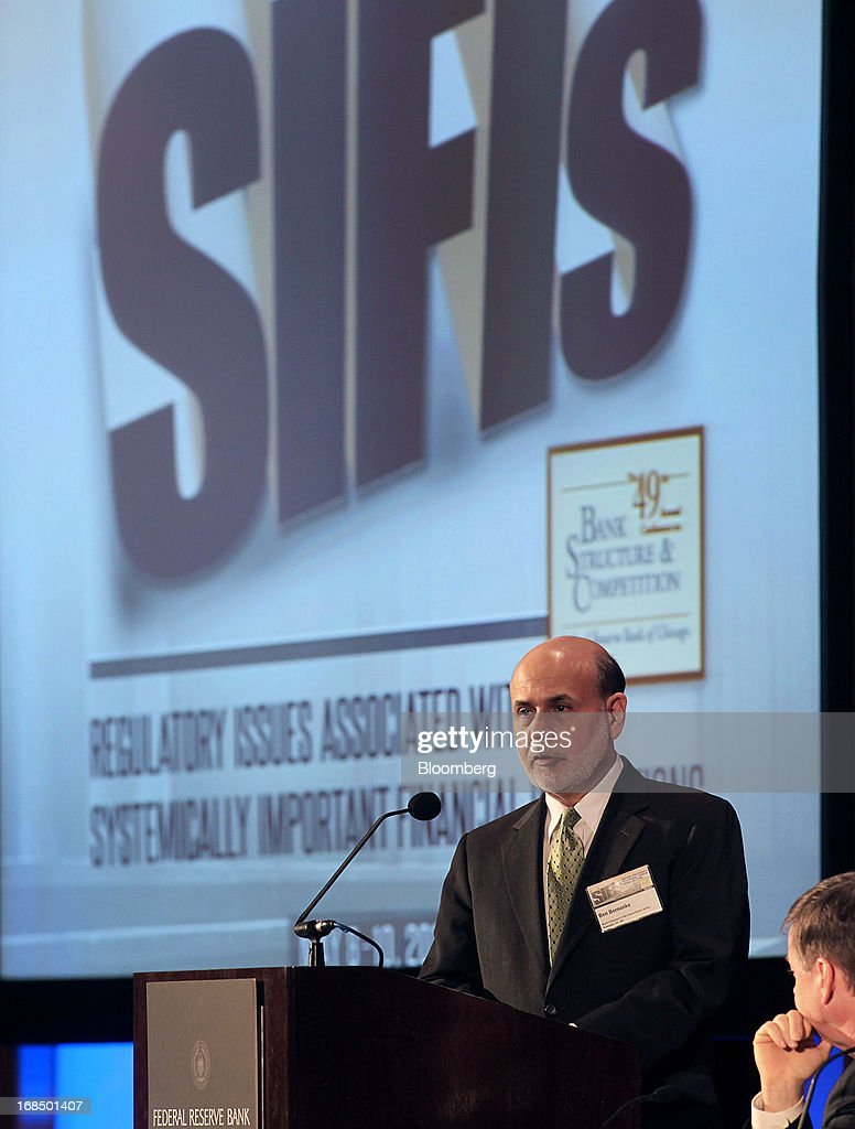Ben S. Bernanke, chairman of the U.S. Federal Reserve, left, speaks while Charles Evans, president and chief executive officer of the Federal Reserve Bank of Chicago, listens during the 49th Annual Conference on Bank Structure and Competition in Chicago, Illinois, U.S., on Friday, May 10, 2013. Bernanke said risks persist in wholesale funding markets used frequently by Wall Street brokers to finance securities trading. Photographer: Tim Boyle/Bloomberg via Getty Images