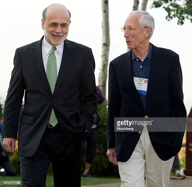 Ben S Bernanke chairman of the US Federal Reserve left walks with Stanley Fischer governor of the Bank of Israel at the Jackson Hole economic...