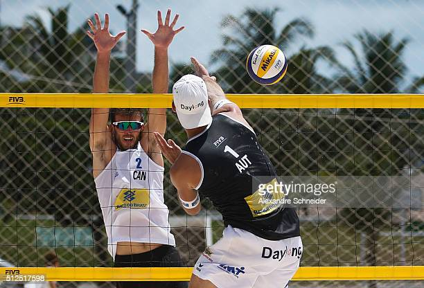Ben Saxton of Canada blocks the ball against Thomas Kunet of Austria during the main draw match at Pajucara beach during day four of the FIVB Beach...