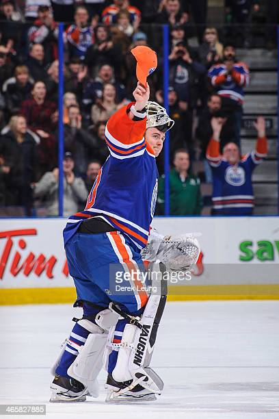 Ben Scrivens of the Edmonton Oilers comes out to give a hat to a person in the crowd after earning the first of three stars after an NHL game against...