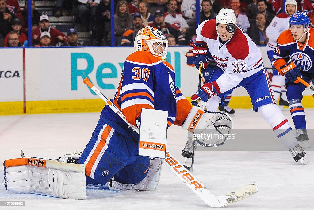 Ben Scrivens of the Edmonton Oilers eyes the puck in front of Travis Moen of the Montreal Canadiens during an NHL game at Rexall Place on October 27...