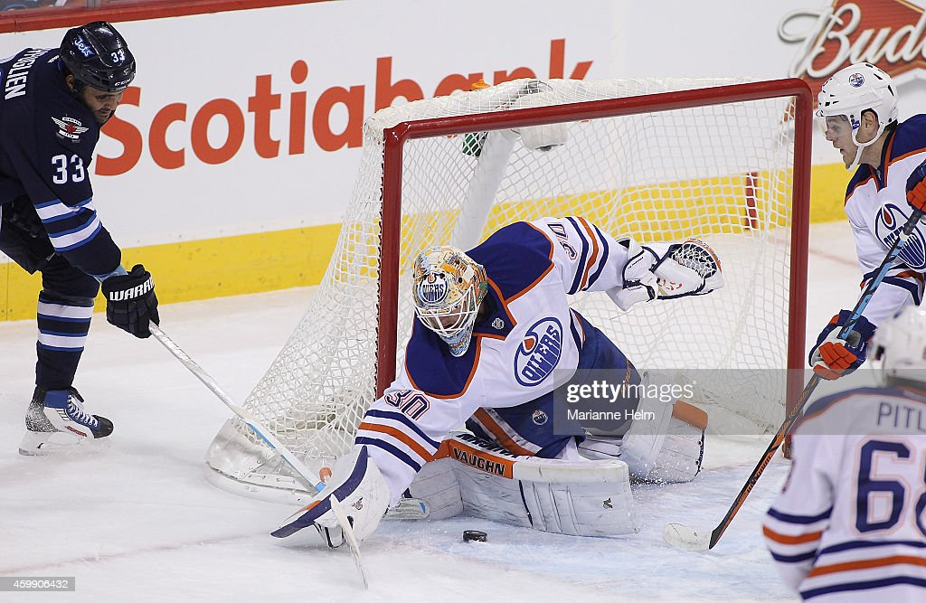 <a gi-track='captionPersonalityLinkClicked' href=/galleries/search?phrase=Ben+Scrivens&family=editorial&specificpeople=7185205 ng-click='$event.stopPropagation()'>Ben Scrivens</a> #30 of the Edmonton Oilers keeps the puck out of the net as <a gi-track='captionPersonalityLinkClicked' href=/galleries/search?phrase=Dustin+Byfuglien&family=editorial&specificpeople=672505 ng-click='$event.stopPropagation()'>Dustin Byfuglien</a> #33 of the Winnipeg Jets tries to score in first-period action in an NHL game at the MTS Centre on December 3, 2014 in Winnipeg, Manitoba, Canada.