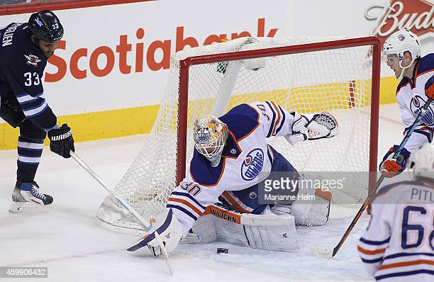 Ben Scrivens of the Edmonton Oilers keeps the puck out of the net as Dustin Byfuglien of the Winnipeg Jets tries to score in firstperiod action in an...