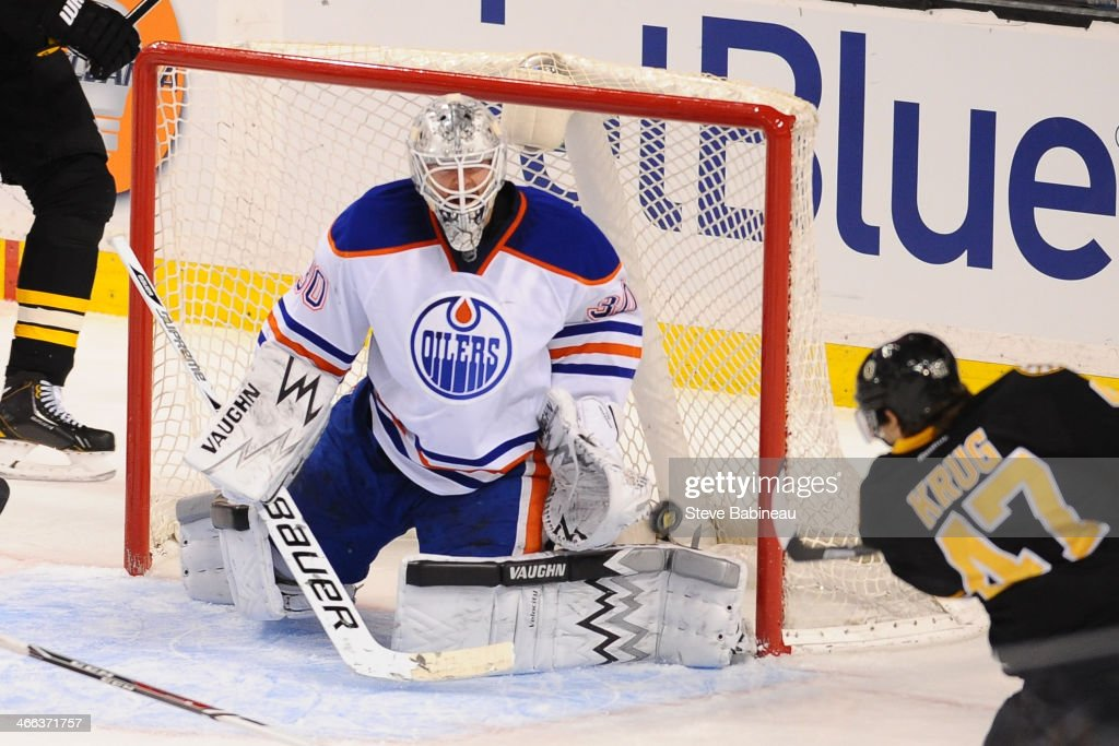 Ben Scrivens of the Edmonton Oilers misses the puck to let in a goal against Torey Krug of the Boston Bruins at the TD Garden on February 1 2014 in...