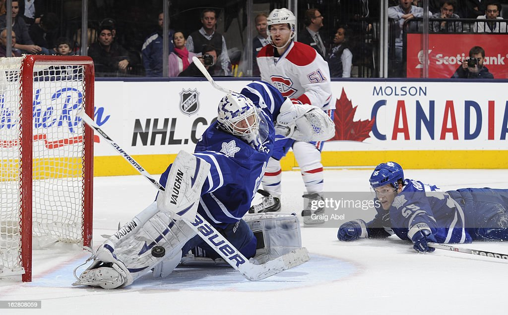 <a gi-track='captionPersonalityLinkClicked' href=/galleries/search?phrase=Ben+Scrivens&family=editorial&specificpeople=7185205 ng-click='$event.stopPropagation()'>Ben Scrivens</a> #30 of the Toronto Maple Leafs makes a pad safe with teammate Korbinian Holzer #55 and <a gi-track='captionPersonalityLinkClicked' href=/galleries/search?phrase=David+Desharnais&family=editorial&specificpeople=4084305 ng-click='$event.stopPropagation()'>David Desharnais</a> #51 of the Montreal Canadiens on the doorstep during NHL game action February 27, 2013 at the Air Canada Centre in Toronto, Ontario, Canada.