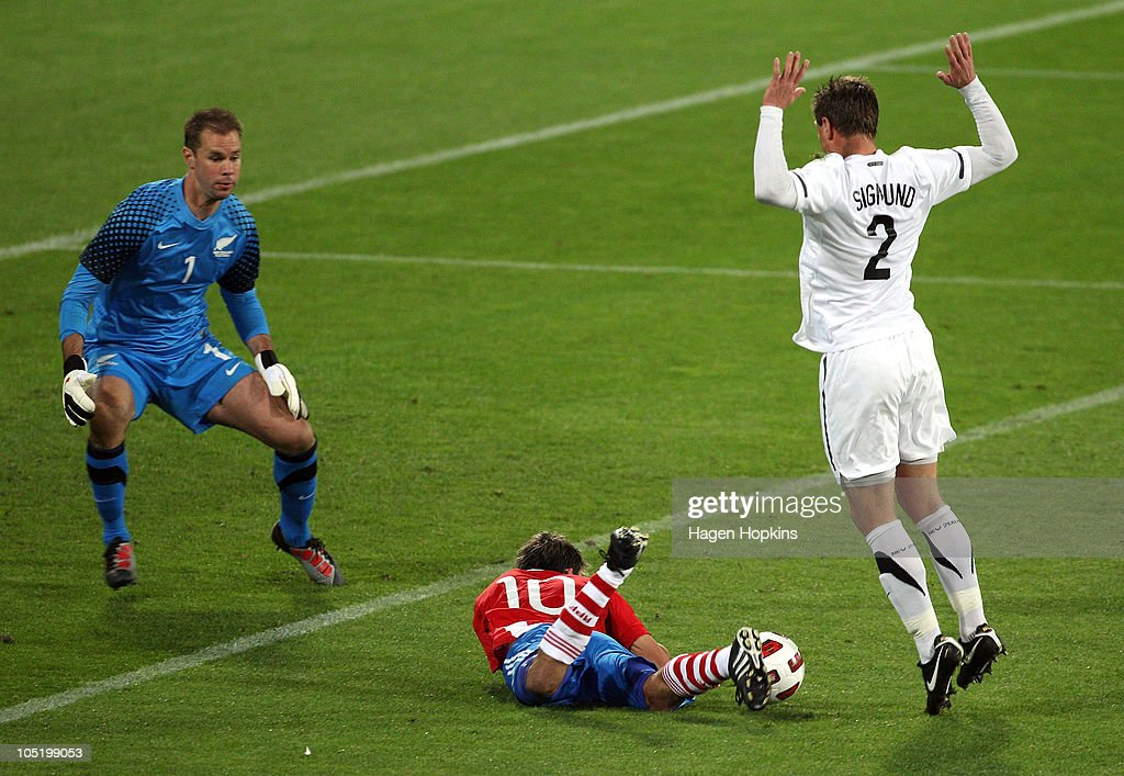 Ben Sigmund of the All Whites brings down Edgar Benitez of Paraguay in the box, resulting in a direct penalty, while Mark Paston looks on during the International Friendly match between the New Zealand All Whites and Paraguay at Westpac Stadium on October 12, 2010 in Wellington, New Zealand.