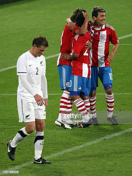 Ben Sigmund of the All Whites looks dejected as Enrique Vera Osvaldo Martinez and Edgar Benitez of Paraguay celebrate a goal during the International...