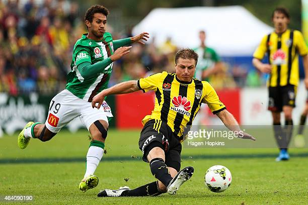 Ben Sigmund of the Phoenix clears the ball under pressure from Mitch Cooper of the Jets during the round 18 ALeague match between Wellington Phoenix...
