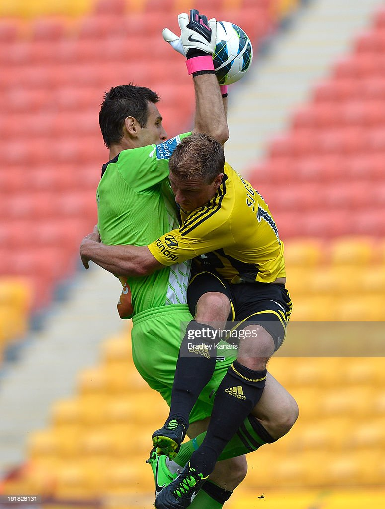 Ben Sigmund of the Phoenix crashes into goal keeper Michael Theo of the Roar during the round 21 A-League match between the Brisbane Roar and the Wellington Phoenix at Suncorp Stadium on February 17, 2013 in Brisbane, Australia.