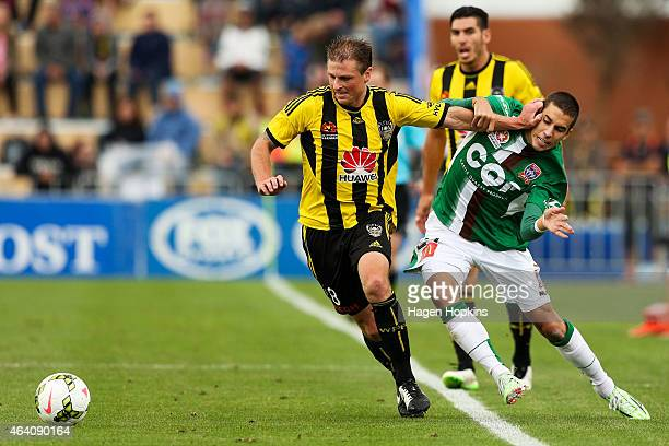 Ben Sigmund of the Phoenix holds off the challenge of Radovan Pavicevic of the Jets during the round 18 ALeague match between Wellington Phoenix and...