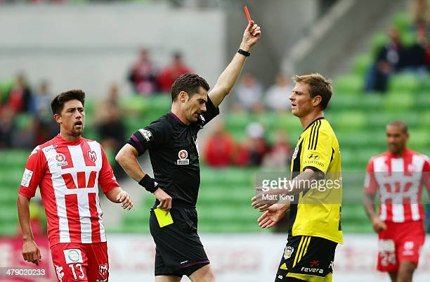Ben Sigmund of the Phoenix is given a red card by referee Ben Williams after his second yellow card for a foul on Harry Kewell of the Heart during...