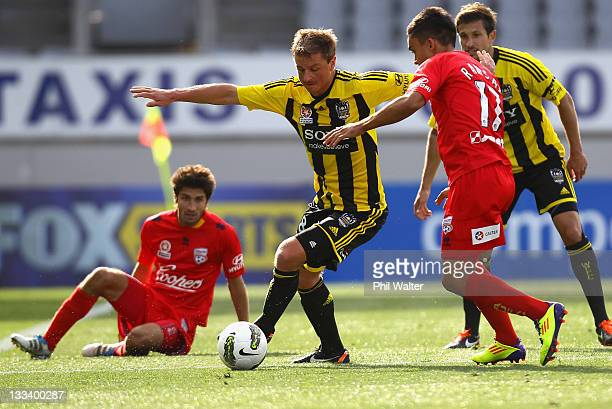 Ben Sigmund of the Wellington Phoenix is put under pressure from Iain Ramsay of Adelaide United during the round seven ALeague match between the...