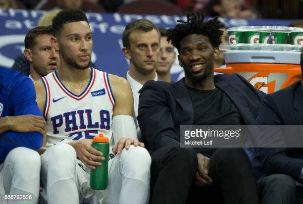 Ben Simmons and Joel Embiid of the Philadelphia 76ers look on from the bench during the preseason game against the Memphis Grizzlies at the Wells...
