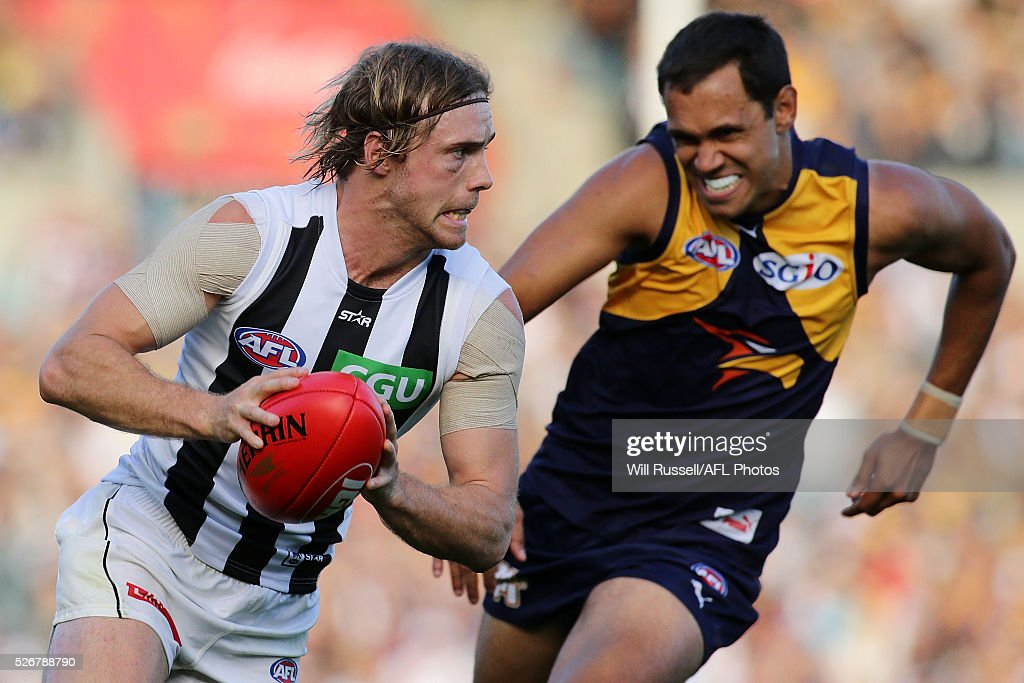 Ben Sinclair of the Magpies runs with the ball under pressure from Josh Hill of the Eagles during the round six AFL match between the West Coast Eagles and the Collingwood Magpies at Domain Stadium on May 1, 2016 in Perth, Australia.