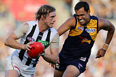 Ben Sinclair of the Magpies runs with the ball under pressure from Josh Hill of the Eagles during the round six AFL match between the West Coast...