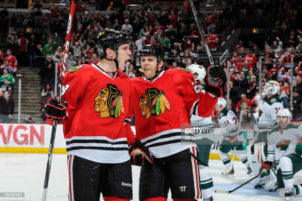 Ben Smith #28 and <a gi-track='captionPersonalityLinkClicked' href=/galleries/search?phrase=Kris+Versteeg&family=editorial&specificpeople=2242969 ng-click='$event.stopPropagation()'>Kris Versteeg</a> #23 of the Chicago Blackhawks react after Smith scored against the Minnesota Wild in the second period during the NHL game on March 03, 2014 at the United Center in Chicago, Illinois.