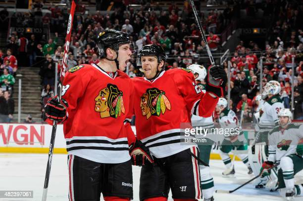 Ben Smith and Kris Versteeg of the Chicago Blackhawks react after Smith scored against the Minnesota Wild in the second period during the NHL game on...