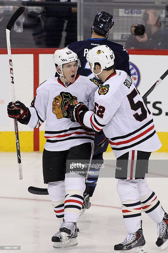 Ben Smith #28 of the Chicago Blackhawks is congratulated by teammate <a gi-track='captionPersonalityLinkClicked' href=/galleries/search?phrase=Brandon+Bollig&family=editorial&specificpeople=7186858 ng-click='$event.stopPropagation()'>Brandon Bollig</a> #52 after scoring a goal in third period action in an NHL game against the Winnipeg Jets at the MTS Centre on November 2, 2013 in Winnipeg, Manitoba, Canada.